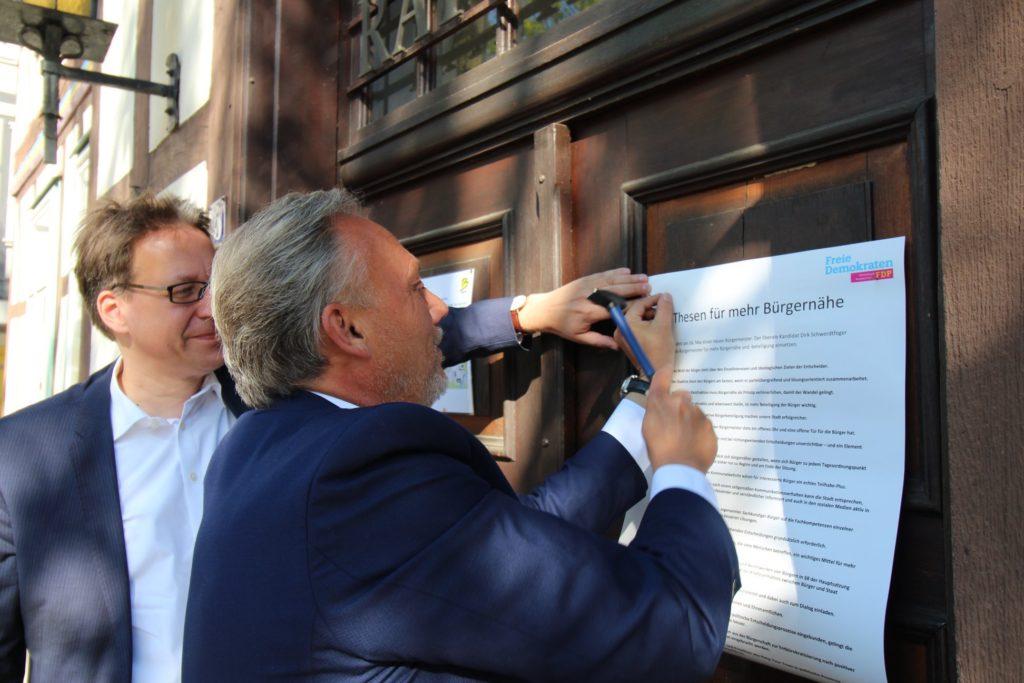 Bürgermeisterkandidat Dirk Schwerdtfeger nagelt seine 20 Thesen für Bürgernähe und Bürgerbeteiligung an die Rathaustür von Burgdorf. FDP Landeschef Dr. Stephan Birkner assistiert.